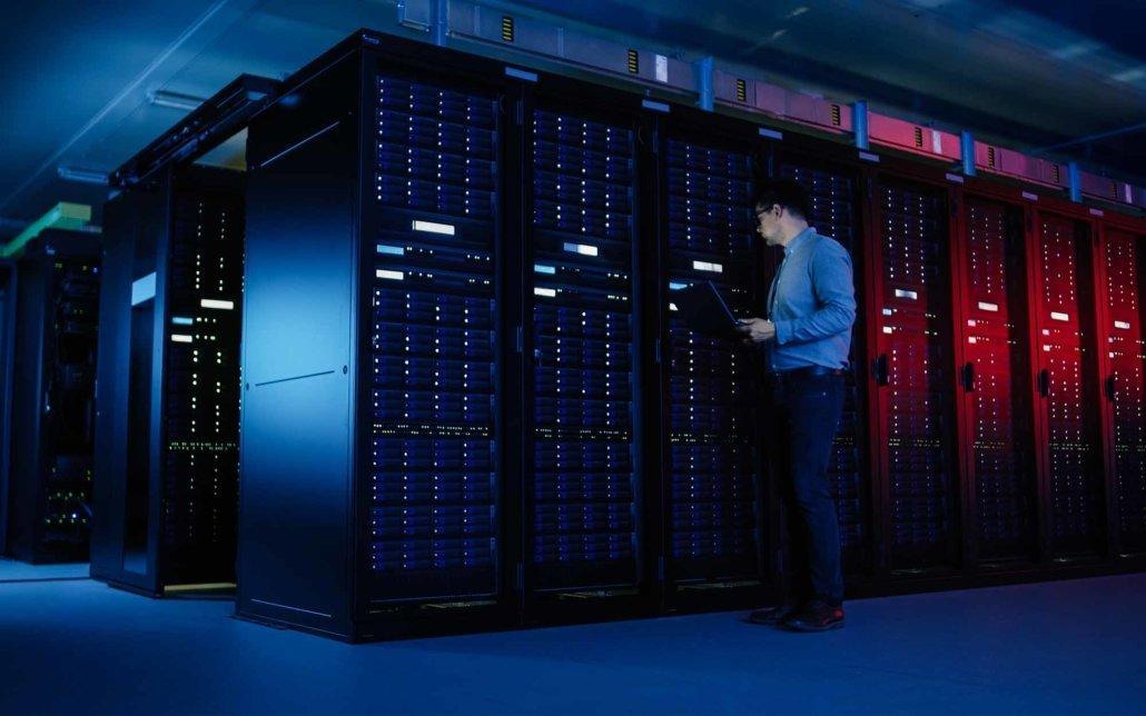 worker looking over server status in dark room