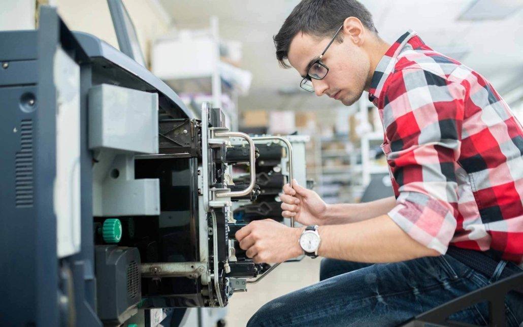 Printer repair worker looking over internal parts